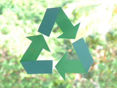 Green recycling symbol painted on a window, representing starting a recycling business.