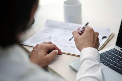 Businessman writing the market analysis section of a business plan at his desk.