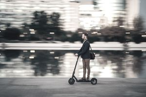 Profile view of businessman riding a scooter on his way to work