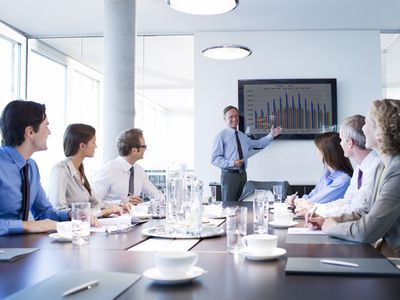 Businessman giving PowerPoint presentation to table of executives