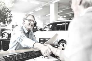 Man shaking hands with his car dealer after making a vehicle purchase