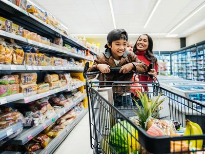 Woman and son pushing a cart together in a supermarket.