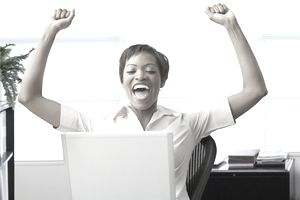 Happy woman cheering at computer in home office