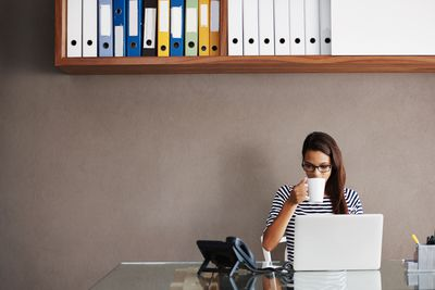 Woman drinking coffee at a laptop in an office