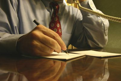 Close-up of businessman's hand writing a letter