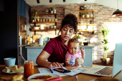 Mother working while holding her daughter