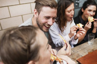 A group of yuccies laughing and eating pizza at restaurant.