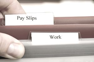 "Close-up of folders with tabs titled ""pay slips"" and ""work"""