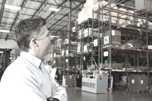 USA, California, Santa Ana, Businessman looking at goods in warehouse