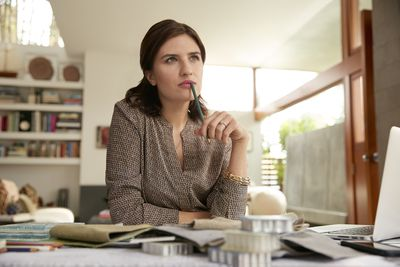 woman sitting at her desk thinking about her business plan for the day.