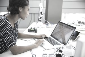 A small businesswoman checks email at a laptop on a crowded design desk.
