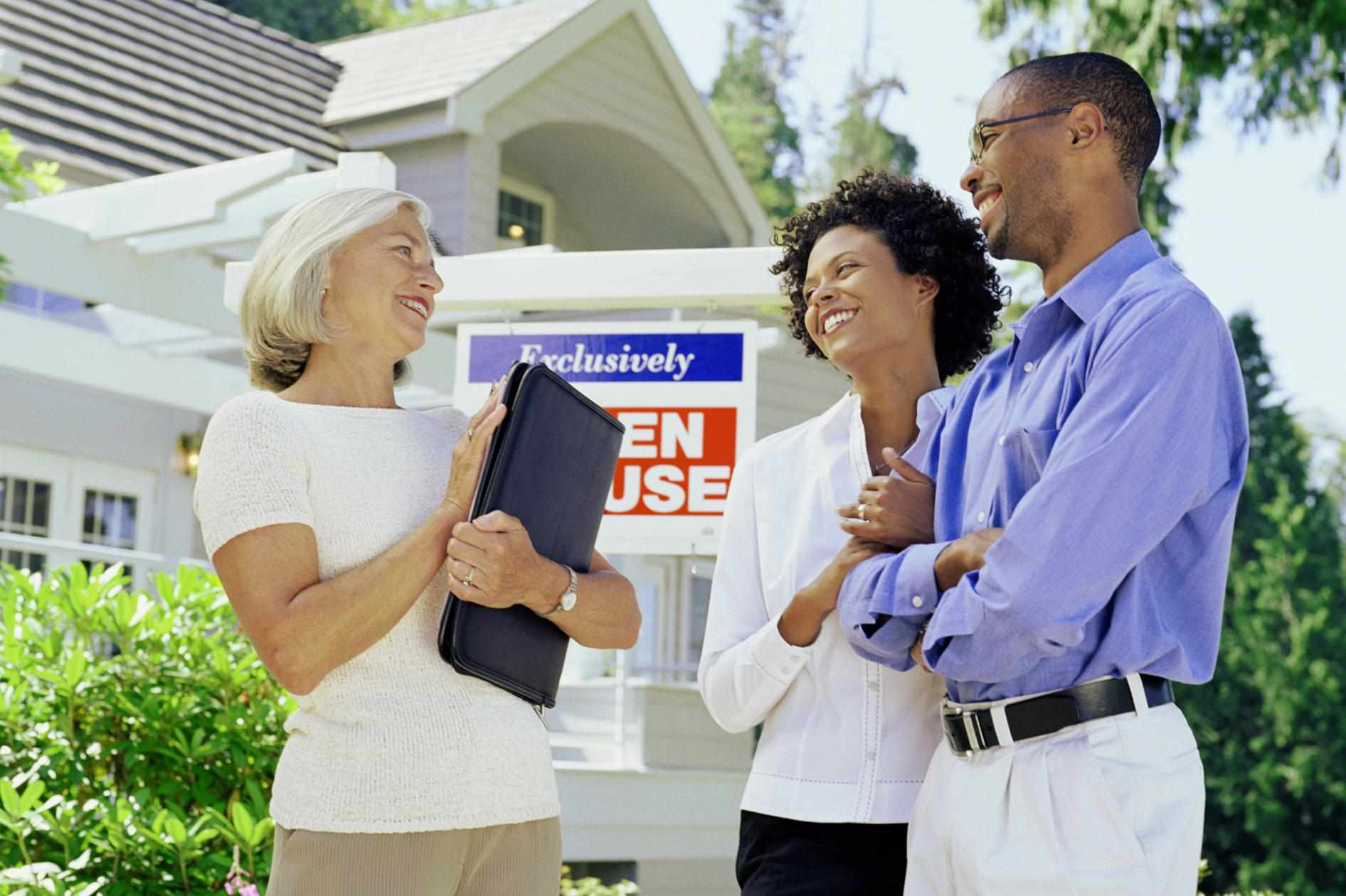 Mature woman standing with couple in front of Open House sign