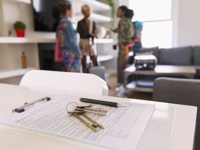 House keys and lease on table in rental office.