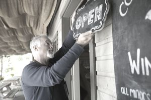 Business owner hanging an open sign