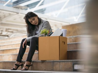 A recently laid-off worker sits on steps beside a cardboard box filled with her belongings.