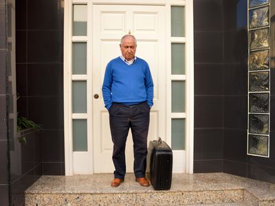 Sad renter standing outside of property with suitcase after eviction