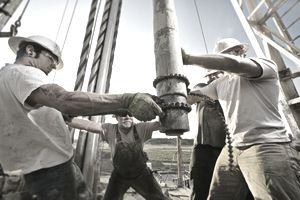 Oil workers using chain to position drill on drilling platform