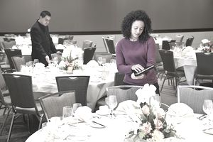 Businesswoman using tablet computer in dining room of a sponsored event