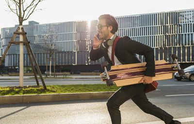 A man in a suit with a skateboard running
