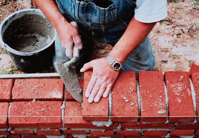 a man laying bricks correctly to prevent cracks forming in walls