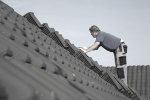 Roofer Shingling a House with asphalt shingles