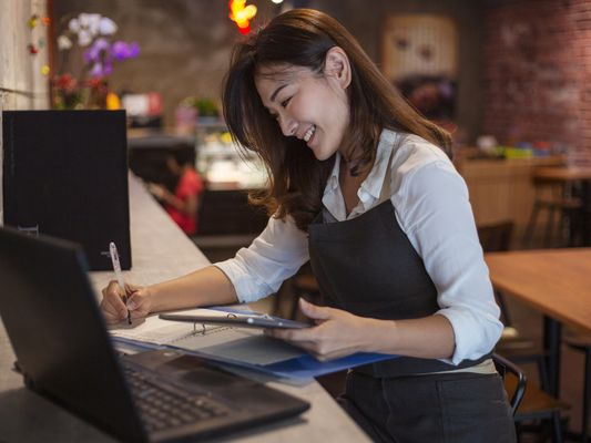 Cafe owner doing accounting bookkeeping