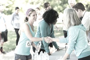 Women shaking hands at a charitable event race.
