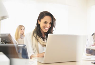Smiling woman using laptop in office