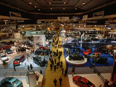 Motor trade show at with attendees and staff interacting around cars on display..