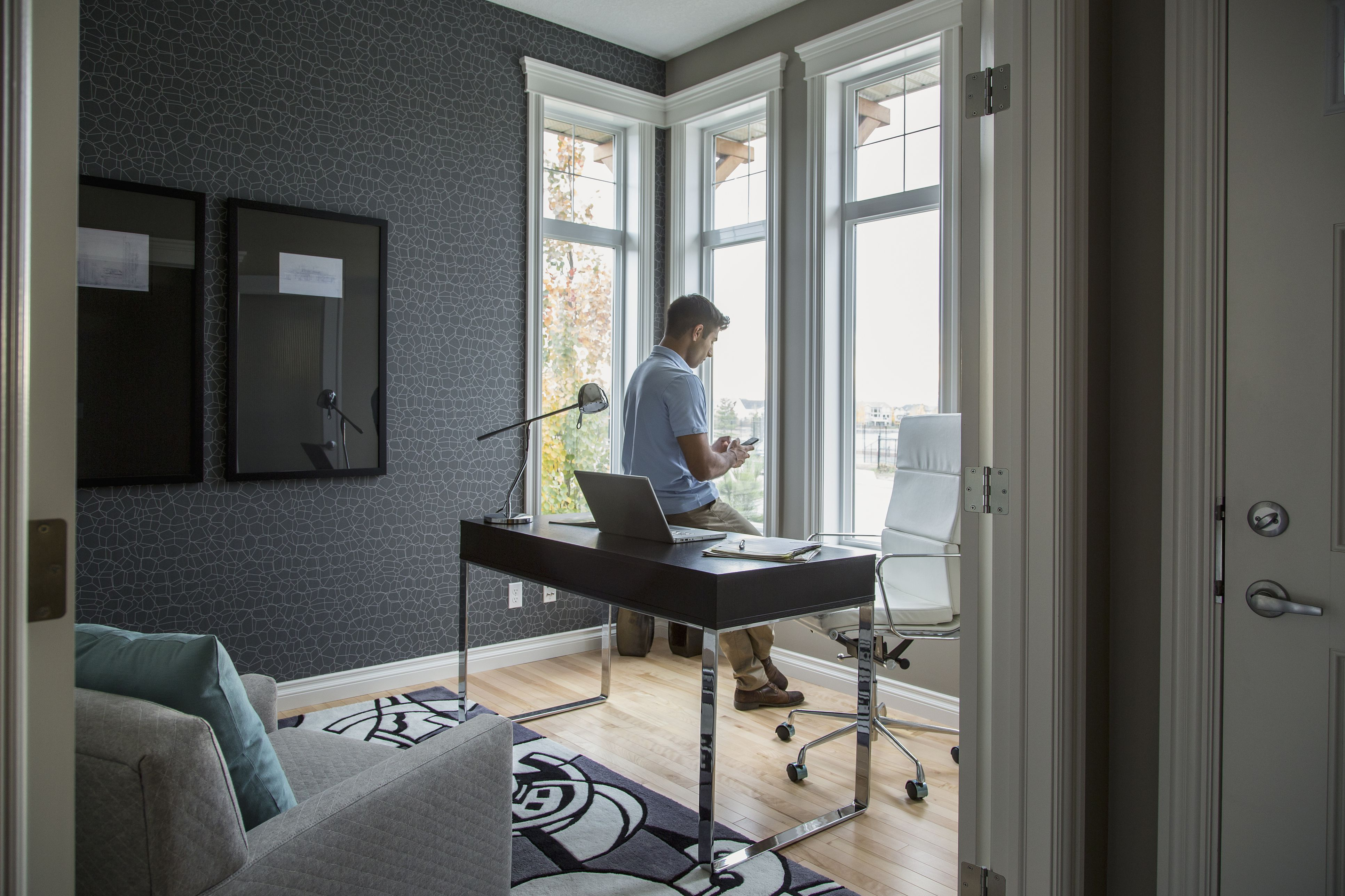 Man text messaging in home office