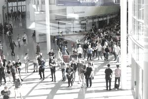 Crowd of people walking at a convention center.