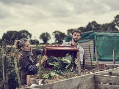 Couple dumping a load into a compost bin.