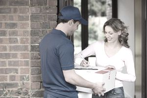 Woman getting a parcel from delivery man