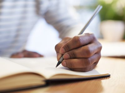 Close up of a man's left hand writing in a notebook with a pen