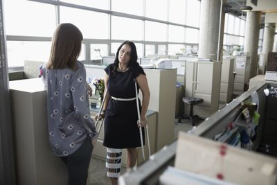 Woman in leg brace on crutches talking to office colleague