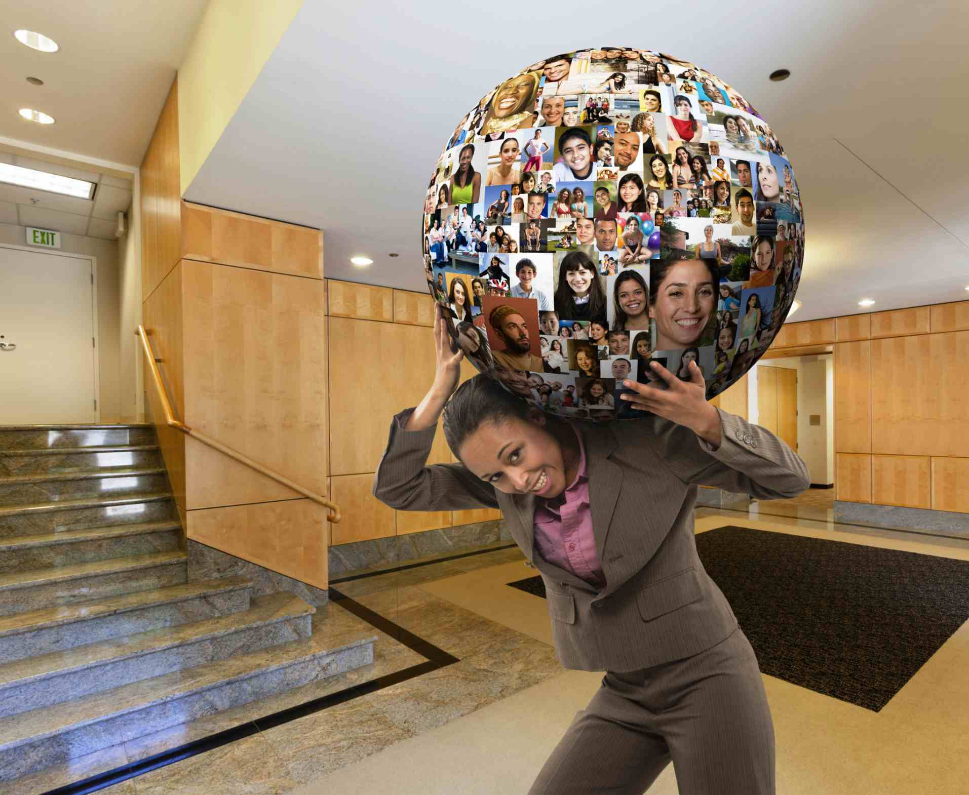 Businesswoman carrying a globe covered in faces on her shoulders
