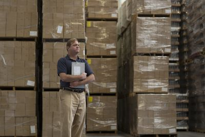 Unhappy business owner in an overstocked warehouse surrounded by dead inventory