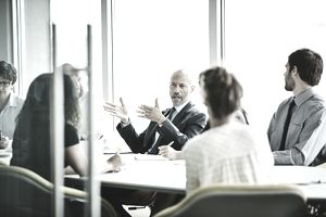 Mature businessman leading meeting in office