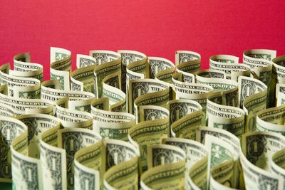 Sea of US 1 dollar bills on red background representing a cash budget.