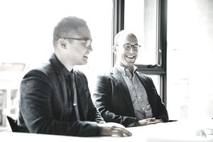 2 businessmen sitting next to each other smiling