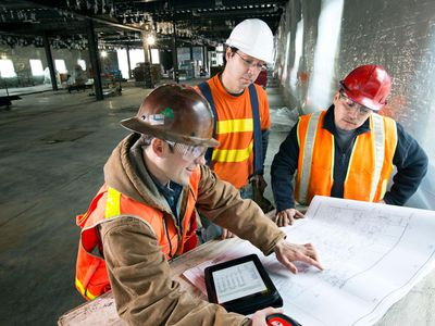 Construction crew looking over blue prints