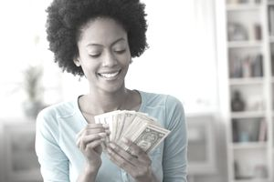 Young woman counting money that she made by optimizing offers on ebay and increasing sales
