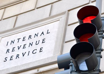 IRS sign with stoplight in foreground.