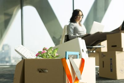 Cardboard box on office floor with businesswoman in background.