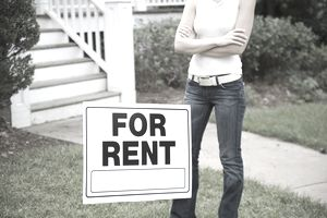 Woman standing next to a for rent sign.