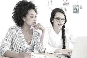 Two young female entrepreneurs analyze their business website