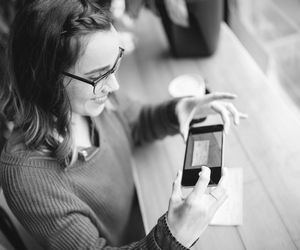 A woman uses her smartphone to deposit her paycheck to her bank.