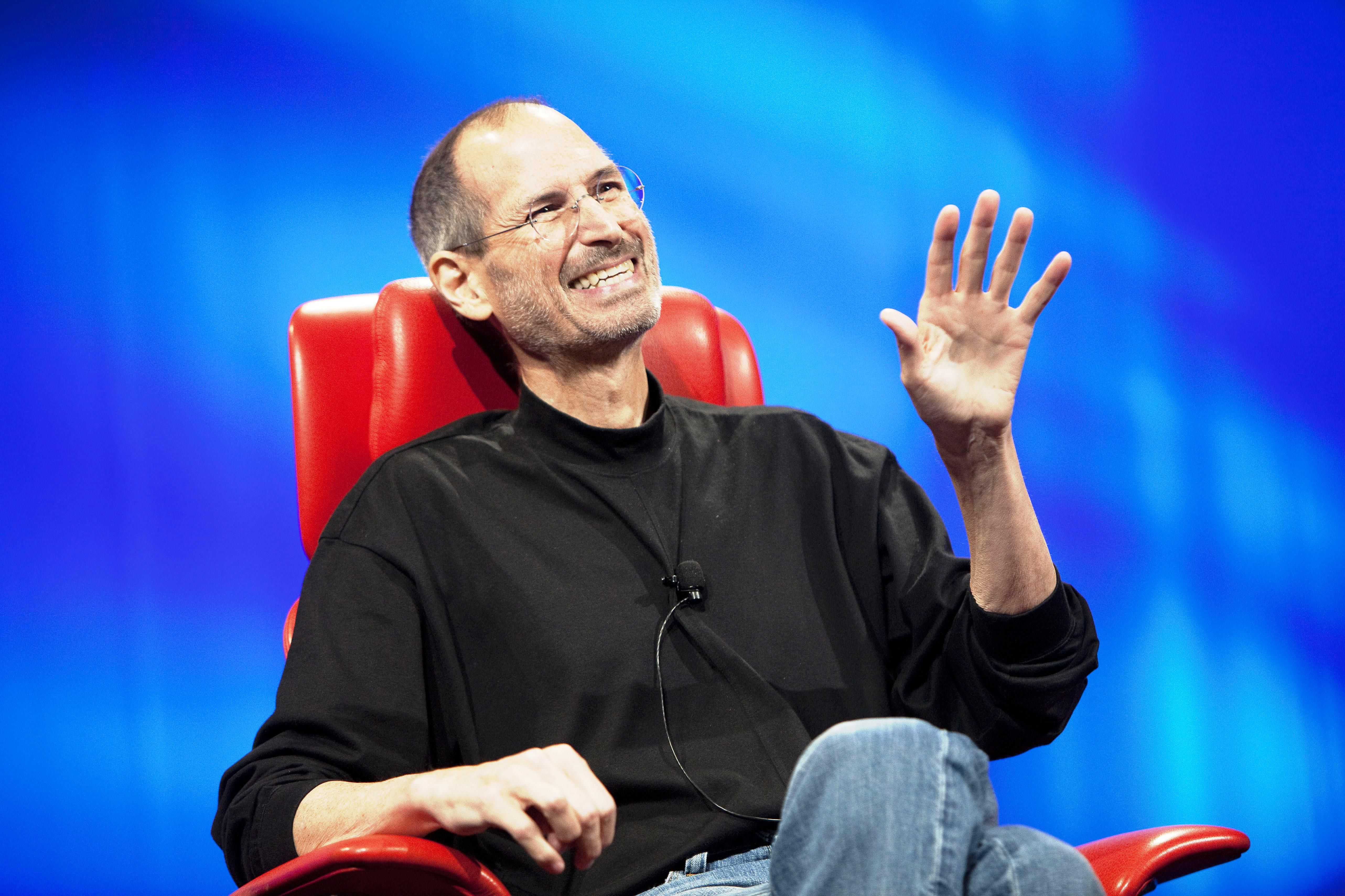 Steve Jobs smiling and talking in a red chair