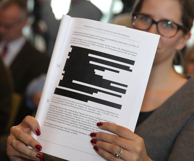 Woman holding a redacted document with portions of text blacked out.