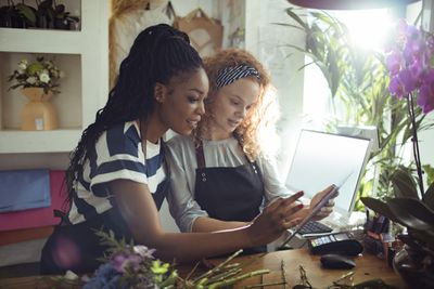 Small business owners managing social media on tablet